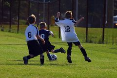 Kids Soccer. Kids playing soccer, defenders chasing down an offensive player stock image