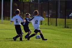 Kids Soccer. Kids playing soccer, defenders chasing down an offensive player royalty free stock photo