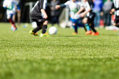 Kids soccer blur. Picture of kids soccer training match with shallow depth of field. Focus on foreground Stock Images
