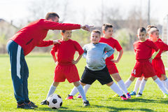 Kids soccer football - children players exercising before match. Kids soccer football - small children players exercising before match on soccer field royalty free stock image