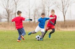 Kids soccer football - children players match on soccer field Stock Photos