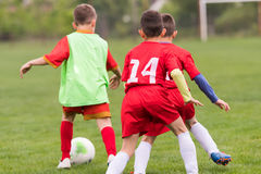 Kids soccer football - children players match on soccer field. Kids soccer football - young children players match on soccer field stock photo
