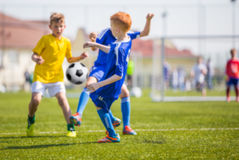 Kids soccer Football Game. Children soccer match. Blurred sport soccer football background. Young boys playing football match. Soccer game between blue and Stock Photos