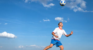 Kids' soccer. Happy boy playing football on sky background royalty free stock photos