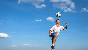 Kids' soccer. Happy boy playing football on sky background stock photo