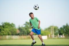 Kids soccer. Little boy running dribbling on the sports field Stock Image