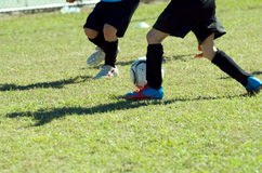 Kids' soccer match. Action shot of children playing a soccer match on grass field Royalty Free Stock Photography