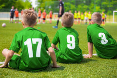 Kids Soccer Players Sitting on the Pitch. Young Boys of Football Team. Sitting on Green Grass Royalty Free Stock Photography
