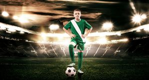 Kid - soccer player. Boy forward in football sportswear on stadium with ball. Sport concept. royalty free stock photography