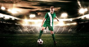 Kid - soccer player. Boy forward in football sportswear on stadium with ball. Sport concept. stock photography