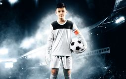Kids - soccer champion. Boy goalkeeper in football sportswear on stadium with ball. Sport concept. Kids in soccer sportswear on stadium with ball stock photography