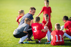 Kids soccer waiting in out with coach Royalty Free Stock Images