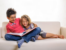 Kids on sofa with big red book Royalty Free Stock Images