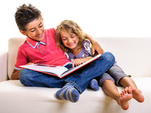 Kids on sofa girl pointing in big red book Royalty Free Stock Image