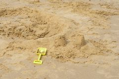 Kids spade by broken sandcastle Stock Photo