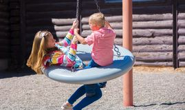 Kids Spin on Playground Swing. Kids playing and spinning at a playground stock images