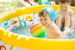 Kids splashing water and having fun in Swim Pool. Little children bathe in yellow Inflatable Swimming Paddling Pool outdoors in hot summer day. Kids splashing Royalty Free Stock Photos