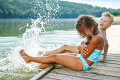 Kids splashing water with their feet Stock Image