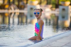 Portrait of cute happy little girl having fun in swimming pool. Kids sport on family summer vacation. Active healthy holiday Royalty Free Stock Photos