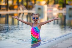 Portrait of cute happy little girl having fun in swimming pool. Kids sport on family summer vacation. Active healthy holiday Stock Photography