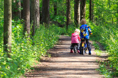 Kids sport - little boy and girl riding bikes in forest Royalty Free Stock Photography