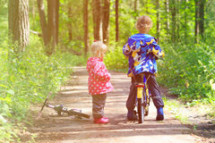 Kids sport - little boy and girl riding bikes in forest Stock Photo