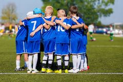 Kids Sport Team Gathering. Children Play Sports. Boys in Sports Jersey Uniforms Having Shout Team. Coach Giving Young Soccer Team Instructions. Youth Sports royalty free stock images