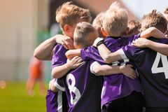 Kids Sports Team Huddling. Group of children in soccer football team standing together before the final game. Boys motivating each other and building sports team royalty free stock image