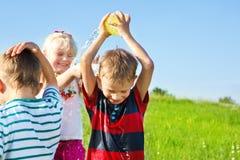 Kids spraying water Royalty Free Stock Photo