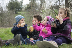 Kids on spring meadow sit on the grass and eat cookies. Stock Image