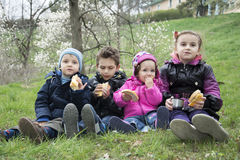 Kids on spring meadow sit on the grass and eat cookies. Royalty Free Stock Image