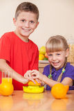 Kids are squeezing orange juice Royalty Free Stock Photography