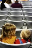 Kids in a stadium. Two children sharing a seat in a stadium Royalty Free Stock Photography