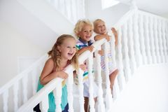 Kids on stairs. Child moving into new home. Kids walking stairs in white house. Children playing in sunny staircase. Family moving into new home. Boy and girl stock photo