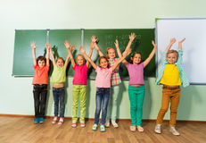 Kids stand with arms up in line near blackboard Royalty Free Stock Photography
