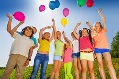 Kids stand in half round with arms up to balloons Royalty Free Stock Images