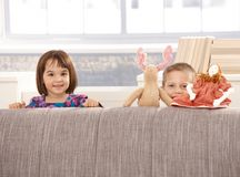 Kids standing behind sofa. With toys, looking at camera, smiling Stock Images