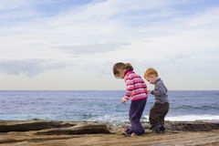 Kids stepping in rockpools Royalty Free Stock Images