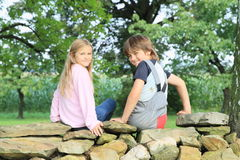 Kids on stone wall. Smiling kids - little girl and boy sitting on stone wall stock photos
