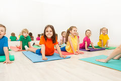 Kids stretching backs on yoga mats in sports club. Group of happy kids, 5-6 years old boys and girls, stretching their backs on yoga mats during gymnastics in Royalty Free Stock Images