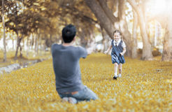 Kids student in uniform running into father`s hands stock image