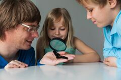 Kids study batterfly through magnifying glass, doing rearch project for school