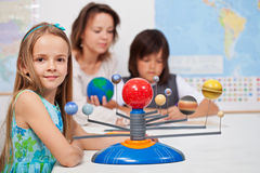 Kids study the solar system under their teacher supervision. Focus on the little girl in front Royalty Free Stock Photography