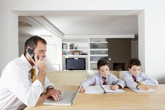Kids studying and Dad working on laptop. Royalty Free Stock Photo