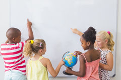 Kids studying globe in classroom Royalty Free Stock Photos
