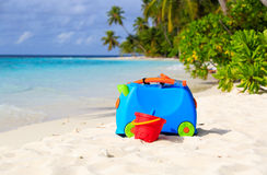 Kids suitcase, toys and snorkel equipment at beach Stock Image