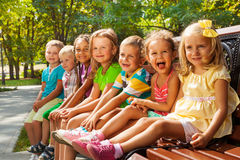 Kids on summer park bench. Close group portrait of little kids, boys and girls sitting together on the bench in the park on sunny day happy and smiling Royalty Free Stock Photo
