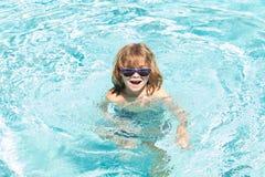 Kids summer vacation. Activities on pool. Having fun at aquapark. Kid swimming in water.