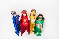 Kids in superhero costumes. High angle view of happy kids in superhero costumes isolated on white Stock Photos