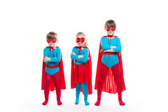 Kids superheroes. Boys and girl characters in costumes posing on white background stock photography